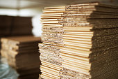 Close up picture of stacks of folded brown cardboard.