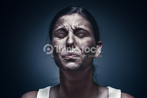 Close up portrait of a crying woman with bruised skin and black eyes : Stock Photo