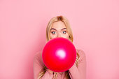 Close up portrait of a funny woman inflating a red balloon for party with wide opened eyes and raised eyebrows, standing over pink background