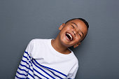 Close up portrait of a happy little boy smiling on gray background