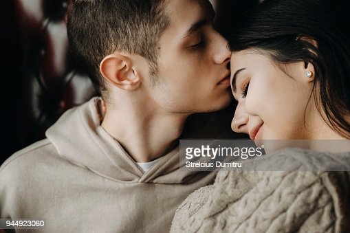 Close up portrait of a lovely young couple sitting on a leather chair while boy is kissing his girlfriend on forehead. : Stock Photo