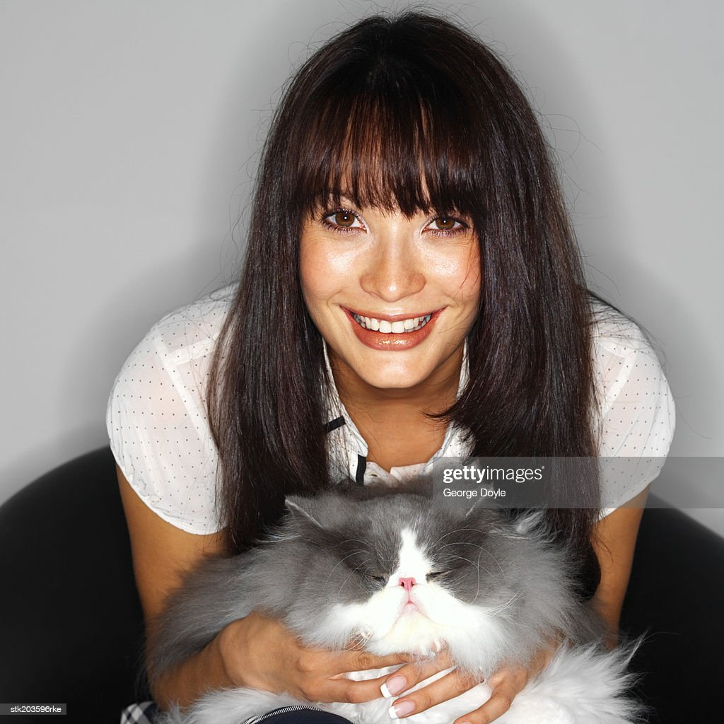 close up portrait of a woman sitting with a cat in her lap : Stock Photo