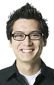close up portrait of a young adult male in a black shirt and glasses as he smiles brightly