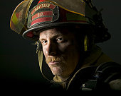 close up portrait of an adult male fire fighter in his helmet as he flashes a stern look