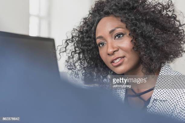 Close up portrait of attractive female businesswoman in her 30s with Afro hairstyle