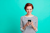 Close up portrait of beautiful cheerful foxy attractive she her lady with telephone in hands gladly using new messenger excited wearing white striped pullover isolated on teal background