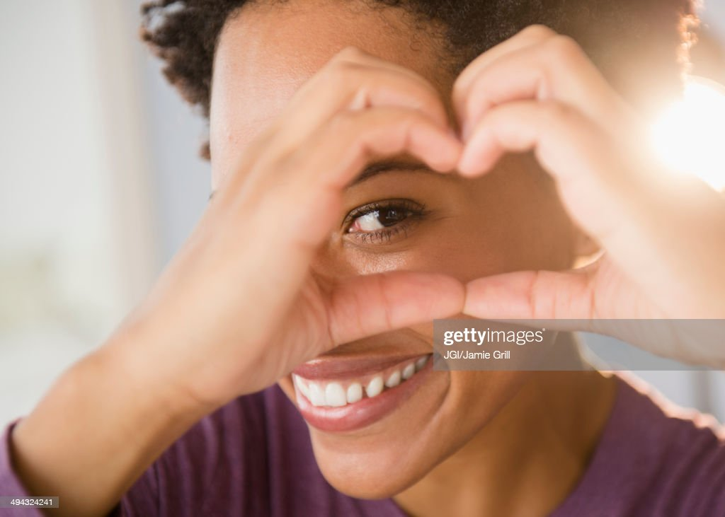 Close up portrait of Black woman forming heart-shape with hands