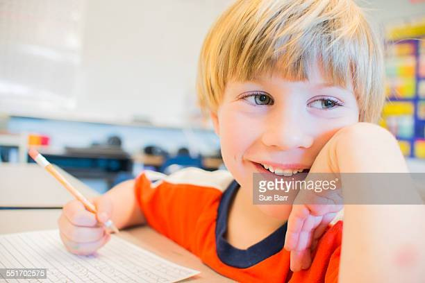 Close up portrait of boy writing in exercise book in classroom