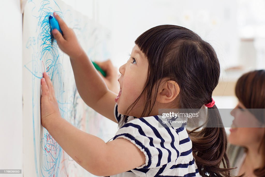 Close up portrait of female toddler having fun drawing : Stock Photo