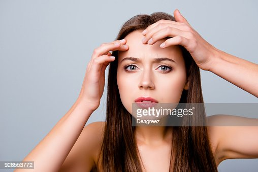 Close up portrait of frustrated sad upset beautiful young woman is squeezing out pimples on her forehead, isolated on grey background : Stock Photo
