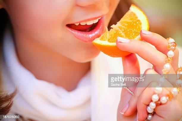 Close up portrait of girl eating orange