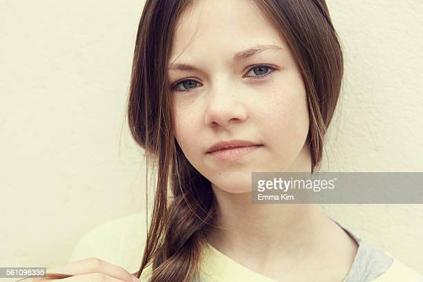 Close up portrait of girl with plaited hair in front of wall