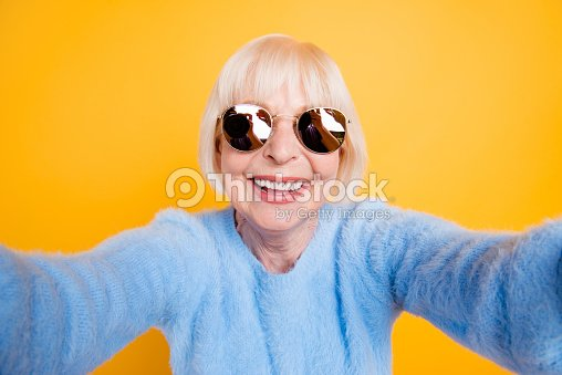 Close up portrait of happy grandma taking a selfie on vacation of two hands, isolated on yellow background : Stock Photo