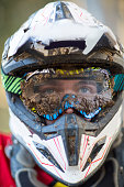 Close up portrait of male motocross racer wearing muddy helmet and goggles