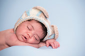 Headshot of 2 weeks old newborn baby sleeping on stomach.
