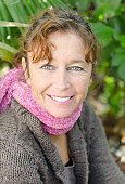 color portrait photo of a happy smiling mature woman with auburn hair and freckles and wearing a pink scarf.