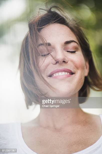 Close up portrait of smiling mid adult woman with eyes closed