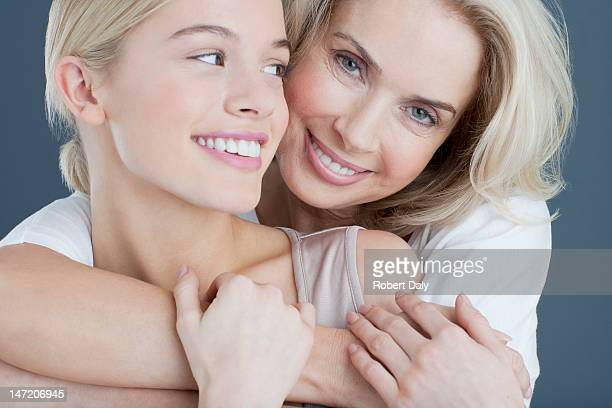 Close up portrait of smiling mother and daughter hugging