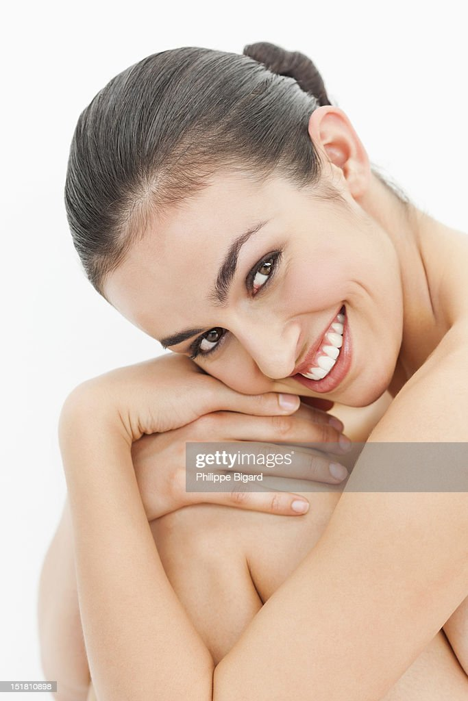 Close up portrait of smiling nude woman hugging knees : Stock Photo
