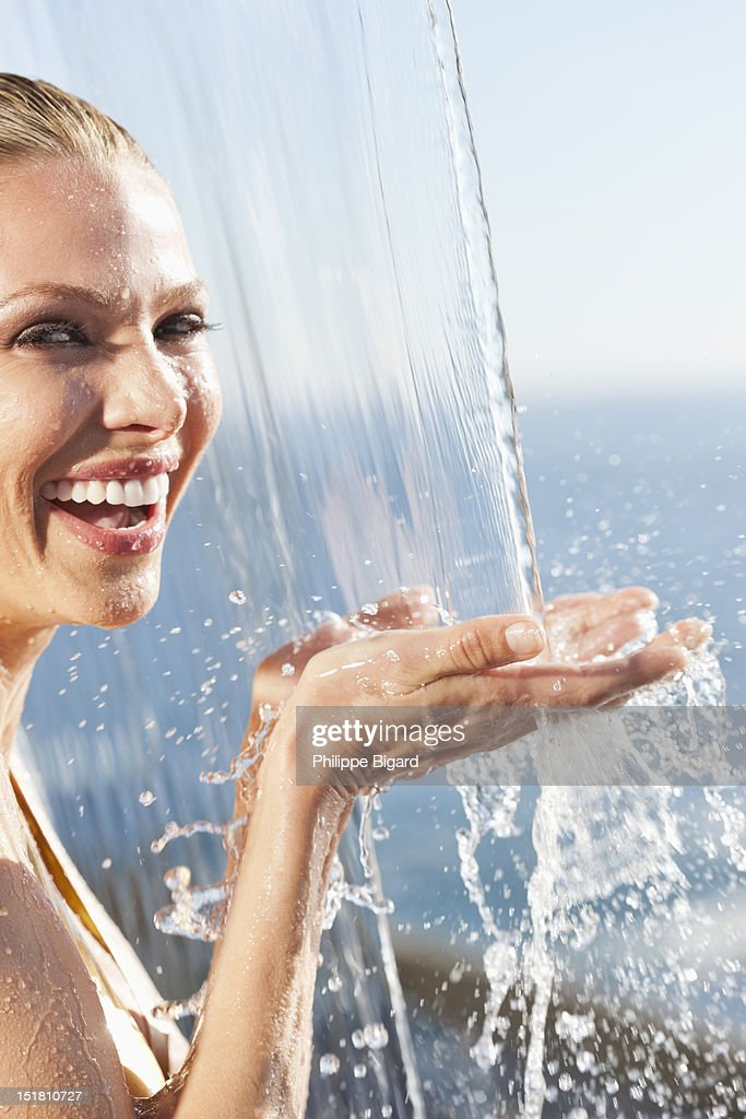 Close up portrait of smiling woman standing under outdoor shower : Stock Photo