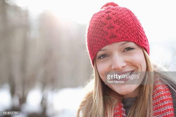 Gros plan portrait de femme souriante portant bonnet en tricot rouge