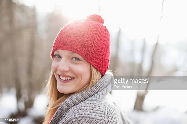 Gros plan portrait de femme souriante en bonnet en tricot rouge