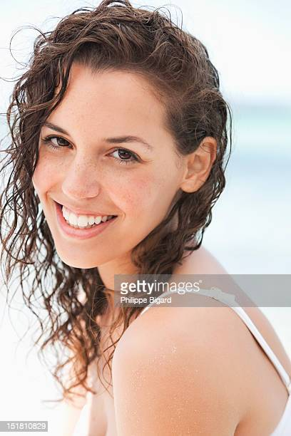 Close up portrait of smiling woman with wet hair on beach