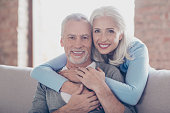 Close up portrait of two happy old married people, they are hugging and have perfect shiny white smiles
