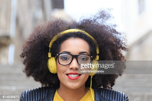 Close up portrait of young woman with yellow headphones