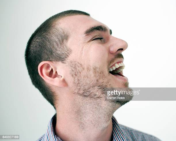 Close up profile of a man laughing