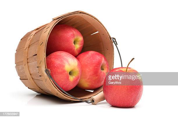 Gros plan des pommes rouges renverser du panier-isolé sur blanc