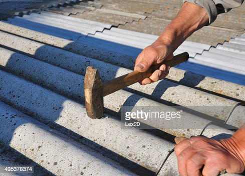 Close Up Roofer Hammering Nail In Asbestos Roof Tiles