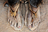 Close up sandy feet of woman in sandals