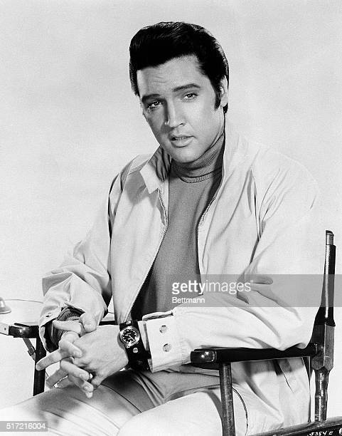 Close up seated portrait of Elvis Presley wearing a turtleneck and zip up jacket