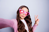 Close up self-portrait of pretty little girl making selfie gesturing peace symbol in casual clothes and  heart-shaped glasses while standing over grey background
