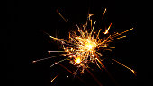 Close up group of several festive firework sparklers over black background, low angle side view, selective focus