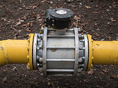 big massive valve on a thick yellow gas water oil steel metal pipelines tubes