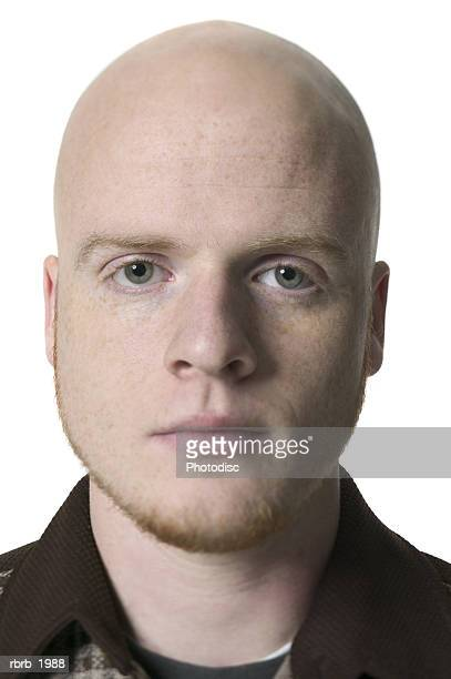 close up shot of a bald young adult male in a brown shirt as he stares into the camera