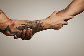 Close up of a forearm Roman, Civil war handshake of two young men, one with tattoos, on white background