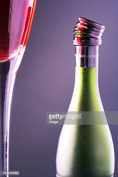 Close up shot of a glass of wine and a bottle