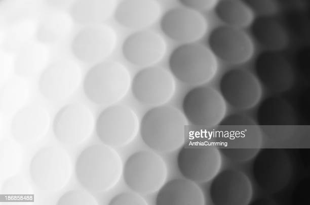 A close up shot of a golf ball, white and fade to dark gray