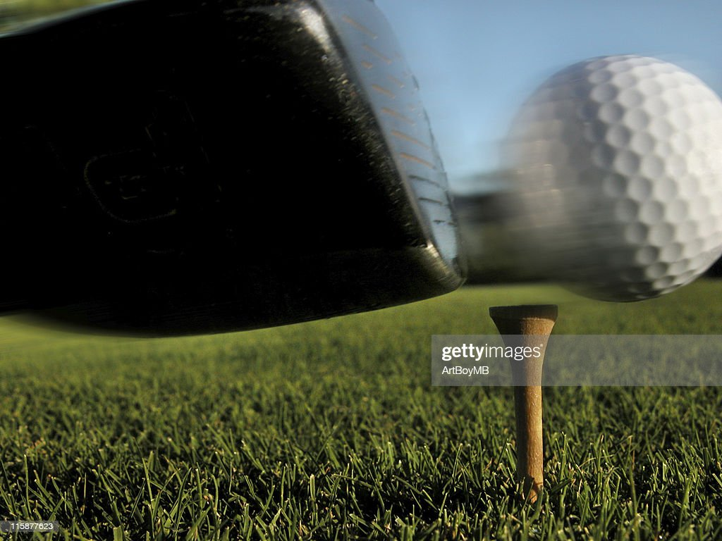 a close up shot of a golf club hitting the ball at the tee stock