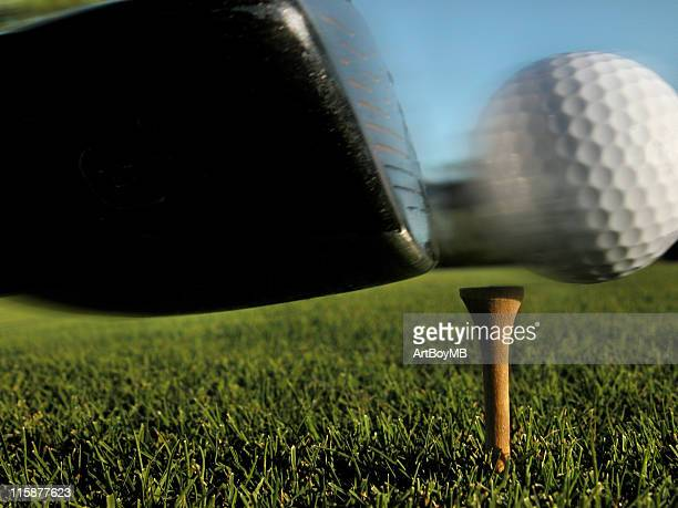 A close up shot of a golf club hitting the ball at the tee