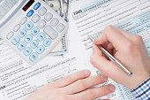 Close up shot of a man filling out 1040 US Tax Form next to calculator and 100 dollars banknote under it