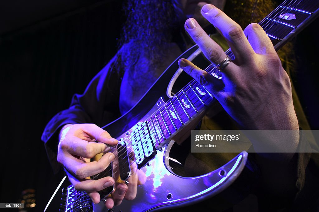 close up shot of an electric guitar as it is played up on stage