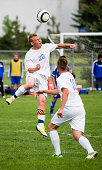 Two soccer players combine with midair ball to create a triangular composition.