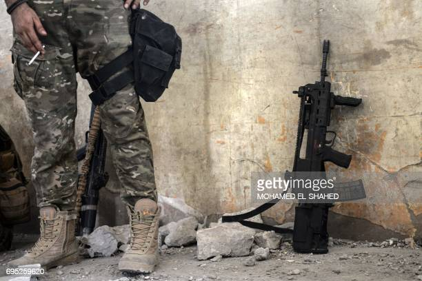 A close up shot shows an Iraqi elite Rapid Response Division member holding a cigarette inside a building in Mosul's western AlShifa district as they...