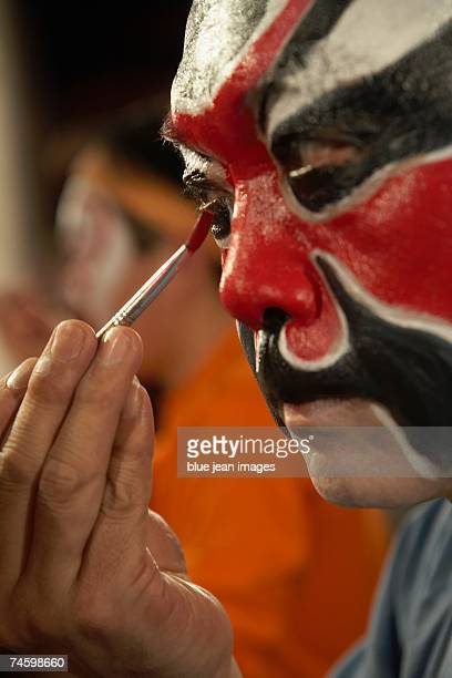 Close up side view of an old actor as he carefully applies traditional Chinese face paint under his eye.