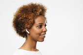 Close up sideways headshot of young smiling african american woman wearing blank white t shirt, listeting to her favourite music track. Copy space for your text