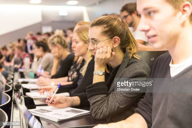 Close up slightly tilt up then slightly zoom out A female student is in the focus she´s writing down notes with her pen while sitting in a crowded...